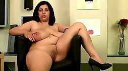 Chubby brunette opens pussy in the armchair
