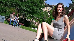 Fabulous young babe in sexy dress flashes her shaved pussy in the park